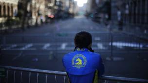 Lizzie Lee of Lynnwood, Washington, pauses near the finish line of Monday's Boston Marathon explosions on 18 April 2013