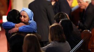 Nun hugs woman at interfaith service