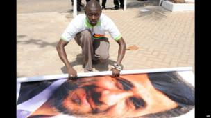 A Ghanaian man rolling up a poster of Iran's president in Accra, Ghana - Wednesday 17 April 2013