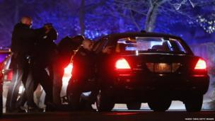 Police with guns drawn search for a suspect