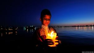 A boy holds a candle in Benghazi