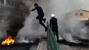 A riot policeman jumps a fence to extinguish a tyre fire set by Bahraini anti-government protesters in Sehla