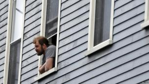 A man looks out of his window in Cambridge, Massachusetts April 19