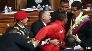 Man is restrained after interrupting Mr Maduro's speech