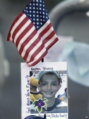 A photograph of bombing victim Martin Richard is attached to a barricade in Boston at a makeshift memorial