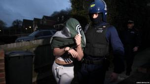Police make an arrest during an early morning raid