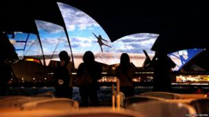 A group of women look at a photograph projected onto the sails of the Sydney Opera House