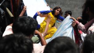 Bangladeshi garment workers assist a survivor after she slid down a length of textile, April 24, 2013.