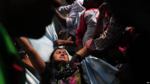 Bangladeshi garment workers assist an injured a survivor after an eight-storey building collapsed in Savar, on the outskirts of Dhaka, on April 24, 2013.