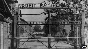 """Auschwitz concentration camp entrance with the sign """"Arbeit macht frei"""" over it"""