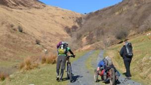Two helps walk alongside a hand cyclist