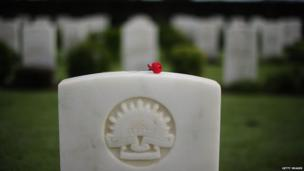 A single red poppy is seen laying on top of a headstone at the Belgian Gardens war cemetery on 25 April 2013 in Townsville, Australia