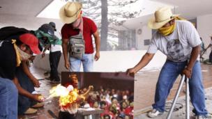 Protesters burn a picture of Mexican President Enrique Pena Nieto