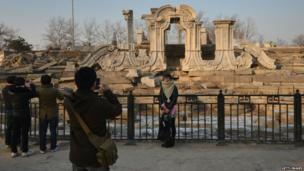 A woman poses for photos at the ruins of the historic Jesuit designed Yuanying Guan (Immense Ocean Observatory) at the Old Summer Palace in Beijing on 6 January 2013