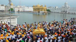Indian Sikhs carry the Guru Granth Sahib, the holy book of the Sikh religion, during a procession near the Golden Temple in Amritsar on 1 September 2011