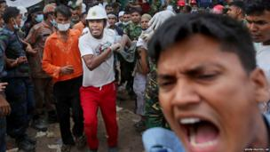 Bangladeshi rescue workers carry a garment worker who was pulled alive from the rubble
