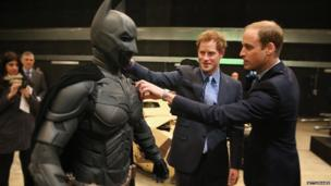 Prince William, Duke of Cambridge and Prince Harry look at a Batsuit