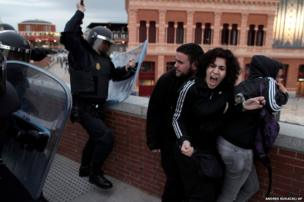 Police clash with demonstrators during a protest near the Spanish Parliament in Madrid