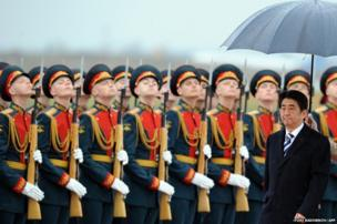 Japanese Prime Minister Shinzo Abe reviews Russian troops as he arrives at Moscow airport