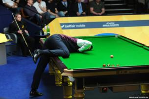 Rickey Walden rests his head on the snooker table as he prepares to play a shot
