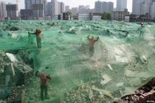Workers install a dust screen on a demolition site