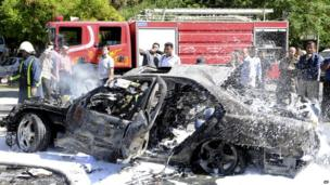 Syrian fire fighters extinguish burning cars after a bomb explodes in Damascus, 29 April 2013