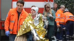 Rescue workers help a woman who was injured in a blast in Prague