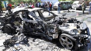 The wreckage of a car at the site of a bomb attack in Damascus, 29 April 2013