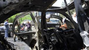 A Syrian officer is seen through the wreckage of a vehicle following an explosion in the Mazzeh district of the Syrian capital Damascus on 29 April 2013