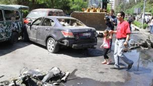 A man leads a little girl past the wreckage and debris of vehicles following an explosion in the Mazzeh district of the Syrian capital Damascus on 29 April 2013