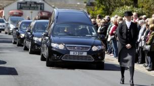 The funeral cortege arrives at the church