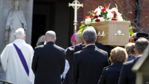 Her coffin is carried to the church