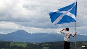 man holds saltire overlooking Scottish hills