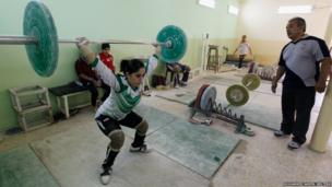 An Iraqi weightlifter lifts a loaded barbell during a training session at a gym in Sadr city in Baghdad
