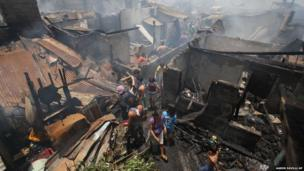 Residents check their homes after a fire in suburban Quezon city, north of Manila, Philippines