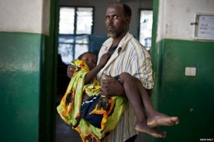 A father holds his son into the isolation unit of Benadir Hospital in Mogadishu, Somalia