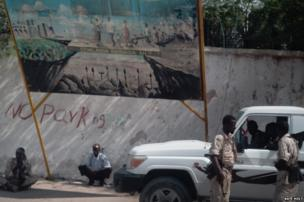 Somali government soldiers stand guard outside Villa Somalia, the presidential palace, next to a poster illustrating the future vision for Somalia