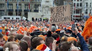 Man holds protest sign in Amsterdam (30 April 2013)