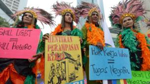 Indonesian transvestites hold placards as they participate in a May Day protest in Jakarta on May 1, 2013.