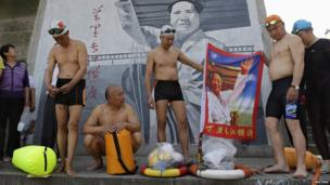 Swimmers hold a flag with an image of the late Chinese leader Mao Zedong, before they set off swimming in the Yangtze to mark International Labour Day in Wuhan, Hubei province, May 1, 2013.