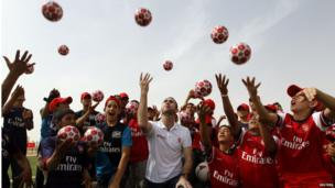 Former Arsenal player Martin Keown and Syrian refugee children celebrate the opening of Save the Children's new football field at al-Zaatri refugee camp on 2 May 2013