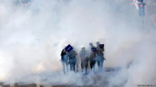 Riot police walk through a cloud of tear gas as they clash with May Day protesters trying to break through barricades to reach the city's main square in central Istanbul