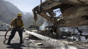 A firefighter puts out the flames that burned a mobile home in Camarillo, California (2 May 2013)