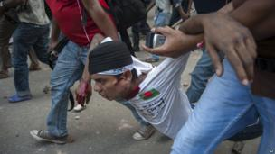 Injured activist is carried away during protests in Dhaka, Bangladesh, on 5 May 2013