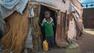 A young boy looking out a makeshift house in a camp in Mogadishu, Somalia