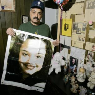 Felix DeJesus holding a banner showing a photograph of his daughter Gina in 2004