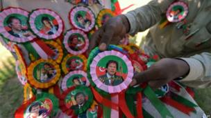 A vendor arranges badges of Pakistani politician and former cricketer Imran Khan