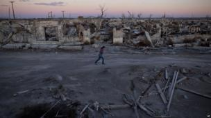 A woman walks through what was a street in Epecuen, Argentina, on 6 May 2013