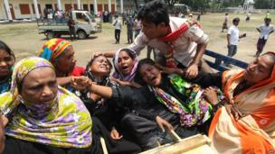 Relatives of a worker who died in the Rana Plaza collapse react after looking into a coffin (9 May 2013)