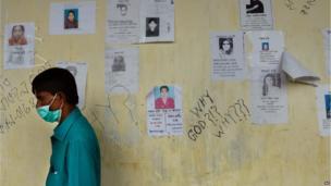 A man walks past missing posters at a makeshift morgue in Savar (9 May 2013)
